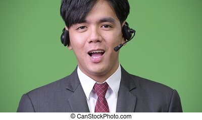 Young handsome Asian businessman working as call center...