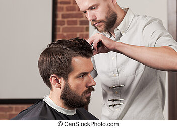 Young handsome barber making haircut of attractive man in barber