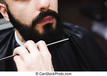 Young handsome barber making haircut of attractive man