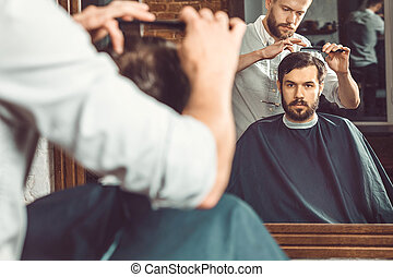 Young handsome barber making haircut of attractive man in...