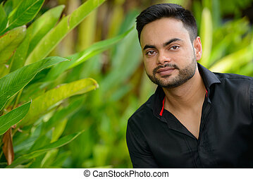 Young handsome bearded Indian businessman at the park