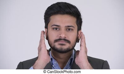Young handsome bearded Indian businessman covering ears as...