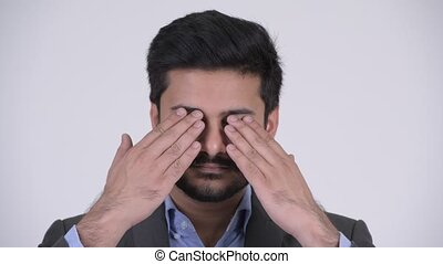 Young handsome bearded Indian businessman covering eyes as...