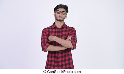 Young handsome bearded Indian hipster man with arms crossed