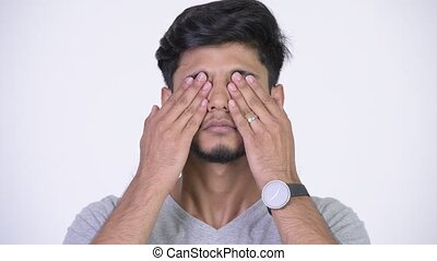 Young handsome bearded Indian man covering eyes as three...