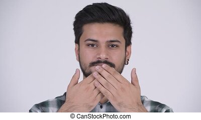 Young handsome bearded Indian man covering mouth as three...