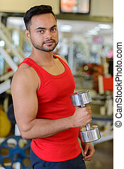 Young handsome bearded Indian man lifting weights at the gym