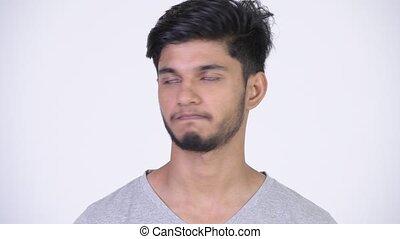 Young handsome bearded Indian man nodding head no - Studio...
