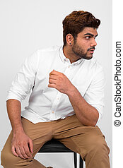 Young handsome bearded Indian man sitting on chair while thinking