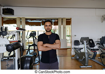 Young handsome bearded Indian man with arms crossed at the gym