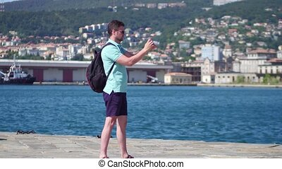 Young handsome bearded man making outdoor photos on the Trieste sea pier