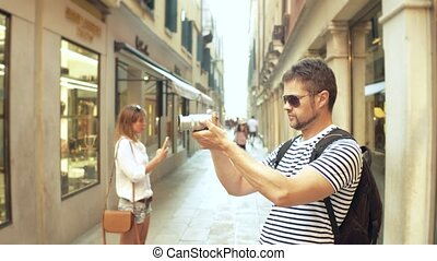 Young handsome bearded man making photos of a narrow street...