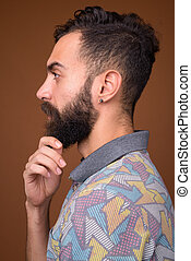 Young handsome bearded Persian man against brown background