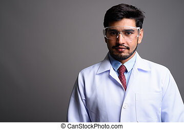 Young handsome bearded Persian man doctor wearing protective...