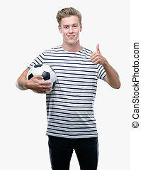 Young handsome blond man holding soccer ball happy with big smile doing ok sign, thumb up with fingers, excellent sign