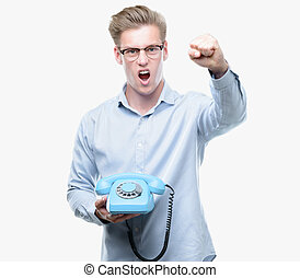 Young handsome blond man holding vintage telephone annoyed...