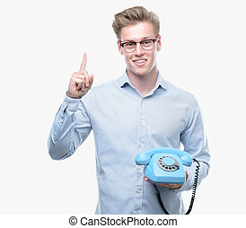 Young handsome blond man holding vintage telephone surprised with an idea or question pointing finger with happy face, number one