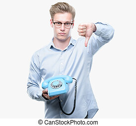 Young handsome blond man holding vintage telephone with...