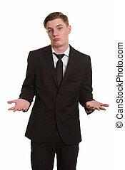 Young handsome blonde businessman in suit shrugging shoulders