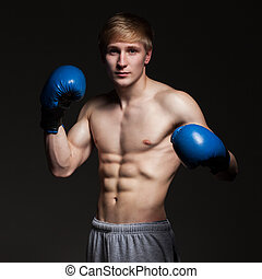 Young handsome boxer in blue gloves