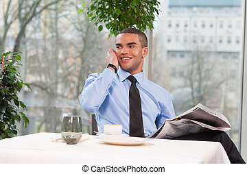 young handsome business man talking on phone. cool guy holding newspaper and smiling