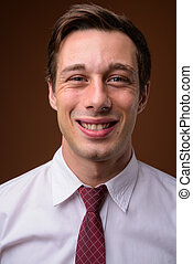 Young handsome businessman against brown background