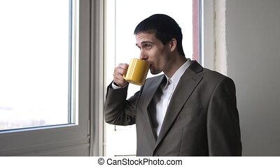 Young handsome businessman drinking coffee and admire view...