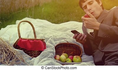 Young handsome businessman having picnic in the park. Man uses mobile phone with basket full of apples. 4k