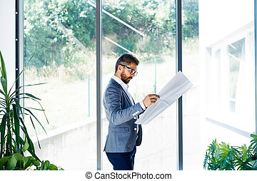Young handsome businessman in his office studying plans.