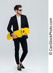 Young handsome businessman in suit and suglasses holding yellow skateboard