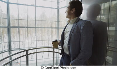Young handsome businessman in suit drinking coffee moving...