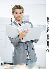 young handsome businessman in suit holding folders