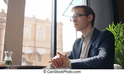 Young handsome businessman is sitting at table in cafe, looking forward, talking, guy in glasses is listening to interlocutor, gesticulating at business lunch in room with window.