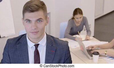 Young handsome businessman is standing in the office with...