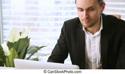 Young handsome businessman looking at laptop screen, smiling and chatting