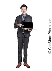 Young handsome businessman standing and holding  laptop .Isolated on white background.