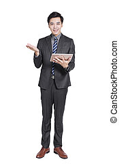 Young handsome businessman standing and holding tablet . Isolated on white background.
