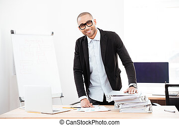 Young handsome businessman standing at the desk in the office