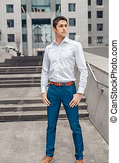 Young handsome businessman standing outside