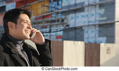 Young handsome businessman talking on a smartphone near the unfinished modern building in the winter. Maybe he is an architect or builder, who has a business talk, or maybe he is just a passerby. Maybe this male is a lover and wait for his beloved woman. He has no hat and gloves, with dark hair, ...