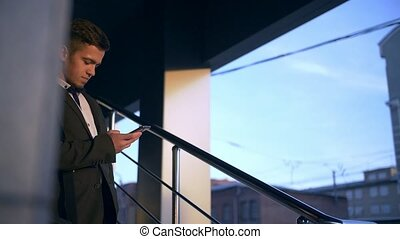 Young handsome businessman talking on mobile phone in the...