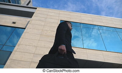 Young handsome businessman with a briefcase walking outdoor along modern office building. Business man in sunglass commuting to work. Confident guy in suit being on his way in city. Slow motion
