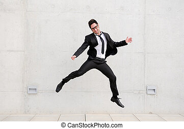 Young handsome businessman with eyeglasses jumping in the street