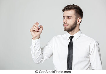 Young handsome businessman writing on a transparent pane.