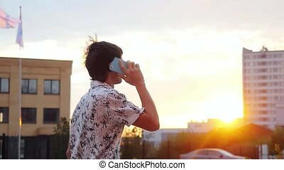 Young handsome caucasian businessman talks mobile phone outdoors at beautiful sunset time. Businessman walking on the city background through the sun with lense flare effects in slowmotion. 1920x1080