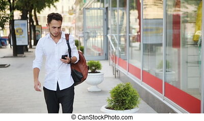 Young handsome caucasian man walking on the street and looking at the smartphone.