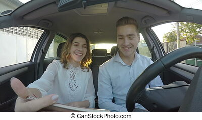Young handsome couple having conversation trough video call in the car on smart phone