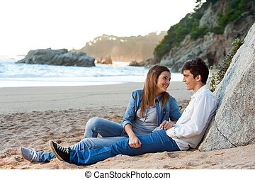 Young handsome couple sitting on beach.