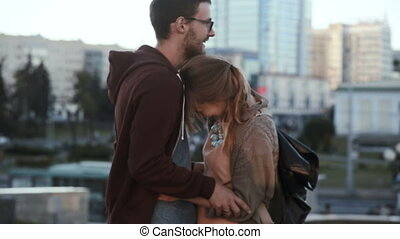 Young handsome couple standing in the city centre and hugging. Happy man and woman on a romantic date in evening. Attractive male and female spending time together in downtown.