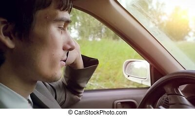 Young handsome dark-haired man driving car in the field and speaking on mobile phone in slowmotion. HD. 1920x1080